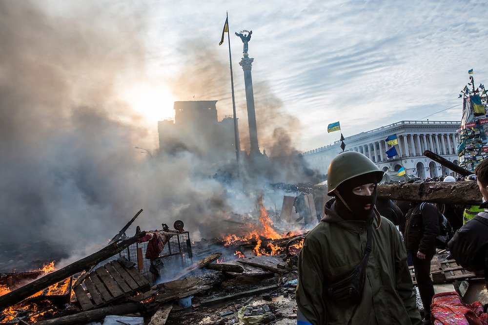 KIEV, UKRAINE - FEBRUARY 19: Anti-government protesters walk amid debris and flames near the perimeter of Independence Square, known as Maidan, on February 19, 2014 in Kiev, Ukraine. After several weeks of calm, violence has again flared between police and anti-government protesters, who are calling for the ouster of President Viktor Yanukovych over corruption and an abandoned trade agreement with the European Union. (Photo by Brendan Hoffman/Getty Images)