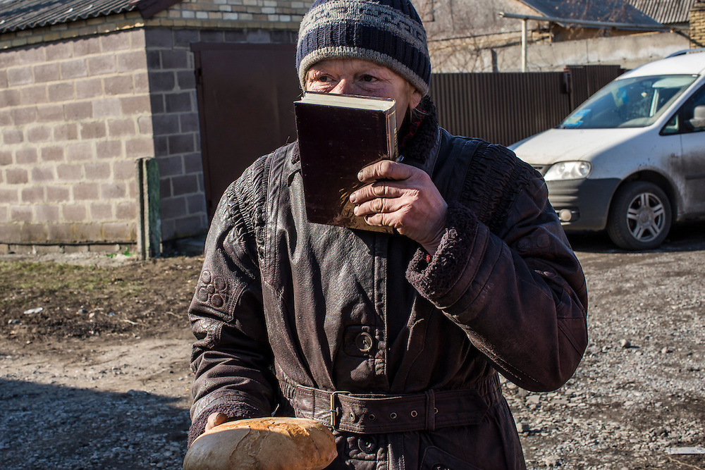 MARIINKA, UKRAINE - FEBRUARY 20, 2016:  Lyudmila Andryusha kisses a bible given to her along with a loaf of bread by volunteers with the Christian Help Center of the Church of the Transfiguration in Mariinka, Ukraine. The Donetsk suburb has been the scene of some of the heaviest fighting recently between Ukrainian forces and pro-Russian rebels. CREDIT: Brendan Hoffman for The New York Times