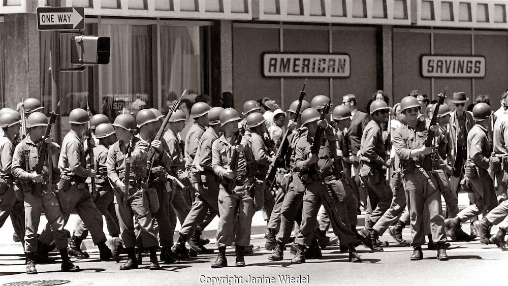 US National guard soldiers with riffles and bayonets take over Berkeley town center as well as The University of California during The  People's Park student protest & riots in  1969.
