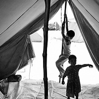 Mehmooda and Moha Rafique play in the tent that has been their temporary home for the past two months. Karachi, Pakistan, 2010