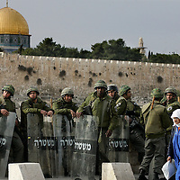 Backdropped by Jerusalem s Dome of the Rock in the old city, a Palestinian woman walks past Israeli security forces taking position in East Jerusalem on January 16, 2009. Photo by Olivier Fitoussi /FLASH90