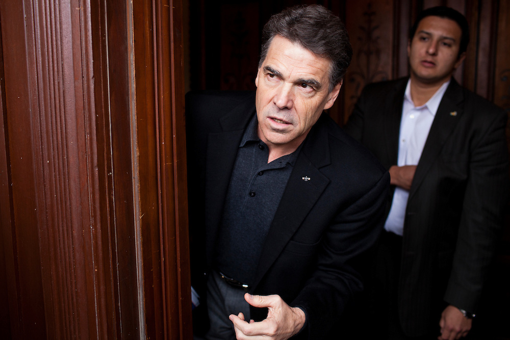 Republican presidential candidate Rick Perry, left, arrives to speak to supporters at Kuhly's Bar & Grill on Thursday, December 22, 2011 in Ottumwa, IA.