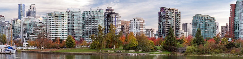 Condo and apartment towers behind the fall foliage in Devonian Harbour Park. Photographed from the Stanley Park seawall along the western end of Coal Harbour in Vancouver, British Columbia, Canada