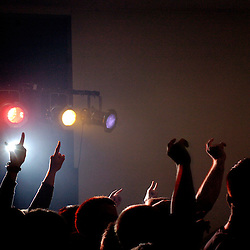 Hands fly in the air in the mosh pit area at a heavy metal show in Iowa.