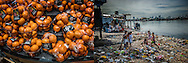 (L): DREAM: Pristine Mandarin oranges wrapped in plastic in a Tokyo supermarket.  Japan  If it is not made from plastic there is a good chance it is wrapped in plastic.  Plastic offers a perfect, shrink-wrapped world in the developed world but that it is clearly a cumulative nightmare for the developed world.  <br /> (R): NIGHTMARE: Children light a toxic fire within a sea of plastic which washes down the Pasig River, Manila's main waterway and comes to rest on the riverbank in the Parolas slum in Tondo.  According to The Straits Times Philippines correspondent, Raul Dancel, one in four of metro Manila's 12 million residents lives in a slum.  Their living environment is contaminated with sewage  and overwhelmed by discarded plastic.  Tondo, Manila, Philippines.