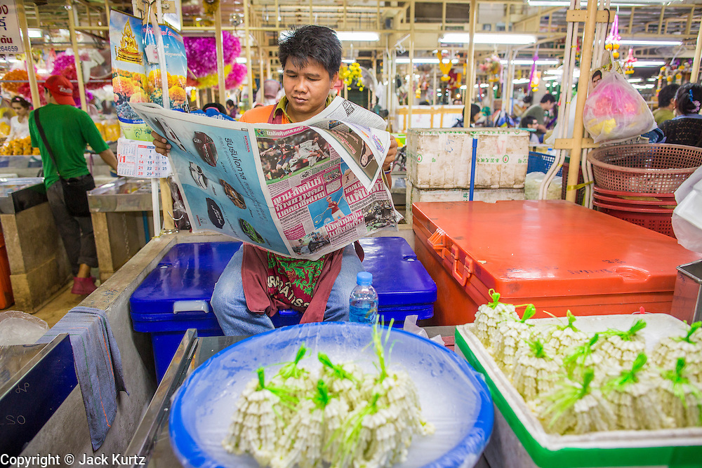 09 OCTOBER 2012 - BANGKOK, THAILAND: A vendor reads the daily newspaper while he waits for customers in the Bangkok Flower Market. The Bangkok Flower Market (Pak Klong Talad) is the biggest wholesale and retail fresh flower market in Bangkok. It is also one of the largest fresh fruit and produce markets in the city. The market is located in the old part of the city, south of Wat Po (Temple of the Reclining Buddha) and the Grand Palace.    PHOTO BY JACK KURTZ
