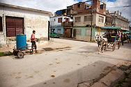 Man with hand cart and coche de caballos in Holguin, Cuba.