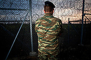 An army officer stands guard at the 12.5-kilometer barbed-wire fence along the land border with Turkey, which was met with skepticism at home as well as from many EU officials, has allegedly succeeded in blocking one of the most  popular transit routes for migrants seeking to make their way to the West.  Image © Angelos Giotopoulos/Falcon Photo Agency