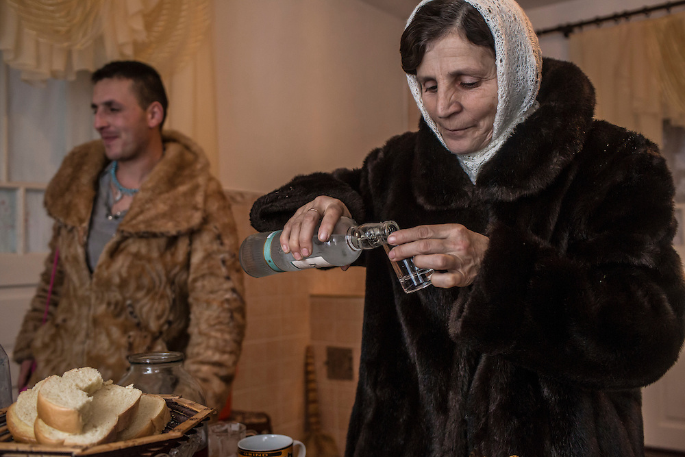 "Olena Istratii, 52, right, pours a shot of vodka after stopping for a break from celebrating the Malanka Festival on Thursday, January 14, 2016 in Krasnoilsk, Ukraine. The annual celebrations, which consist of costumed villagers going in a group from house to house singing, playing music, and performing skits, began the previous sundown, went all night, and will last until evening. ""Everybody's coming from abroad for Malanka. It's a very big holiday. My mother, my grandmother, and my great-grandmother did it too. We will do everything we can so the tradition will not disappear,"" she says."