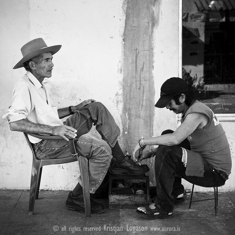 Elderly man in Suchitoto getting a shoe shine