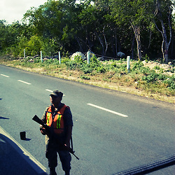 Inspecting passing cars for drugs and other illegal items, a team of Mexican soldiers is armed with assault rifles.