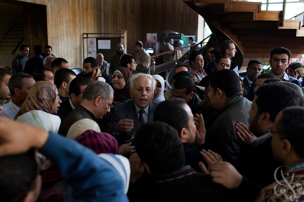 A top editor, Abdul Azeem Darwish(c) tries to calm a group of protesters February 09, 2011 in the lobby of Al Ahram, the country's semi-official newspaper in downtown Cairo, Egypt. The protesters, part-time employees at the paper were critical of the paper's recent anti-democracy movement coverage and were also hoping to gain concessions that would elevate them to full-time workers.   (Photo by Scott Nelson).