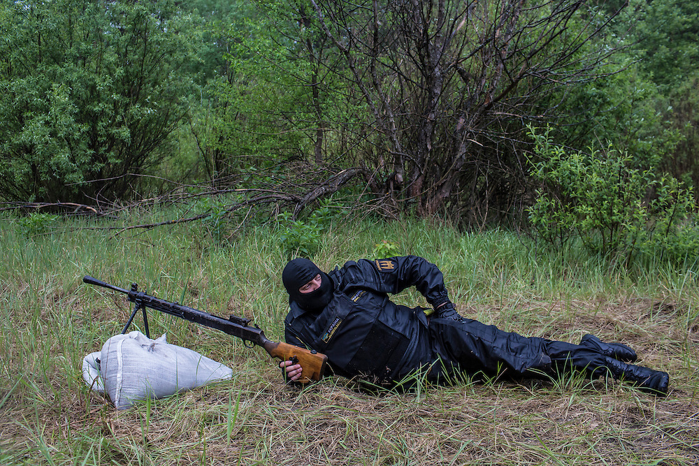 DNIPROPETROVSK REGION, UKRAINE - MAY 19: A man demonstrates use of a gun at a training camp for the Donbass Battalion, a pro-Ukrainian militia, on May 19, 2014 in Dnipropetrovsk Region, Ukraine. A week before presidential elections are scheduled, questions remain whether the eastern regions of Donetsk and Luhansk are stable enough to administer the vote. (Photo by Brendan Hoffman/Getty Images) *** Local Caption ***