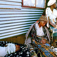 South Africa, Boipatong, 1992..The aunt of nine month old Aaron Mathope sits next to his body in Boipatong township south of Johannesburg June 1992 on the day 45 people were killed by Inkatha Freedom Party supporting Zulus.  Aaron and his mother were hacked to death, and the Truth & Reconciliation Commission found both Inkatha and the security forces of the then-white regime responsible.  .Photograph by Greg Marinovich