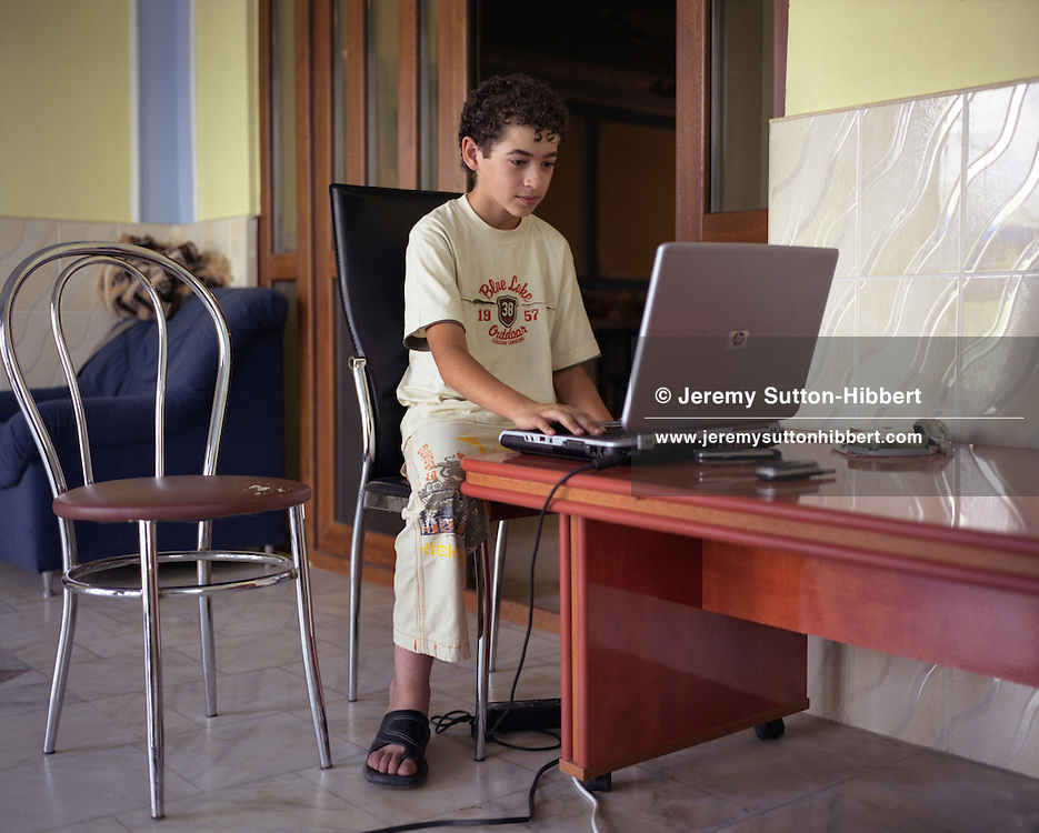 Florin 'Ciprian' Lulu, aged 13, plays on his laptop burning CD's of music,  in his parent's home, in the village of Sintesti, in Romania, early August 2006. One month after this picture Florin 'Ciprian' would be marrying 14 year old Garoafa Mihai. The computers exist primarily ( I am told) as a way for the Roma to check the daily stock exchange values of certain metals, but in reality are usually not connected to the internet, nor does anyone have the necessary knowledge to use them.  The Kalderari roma of Sintesti are by tradition metal workers, originally making alcohol stills, pots and pans, but now dealing in scrap metal. The large profits from their business have enabled them to build large houses in the village of Sintesti, 20km from Bucharest, and to invest in fast, Western brand name cars such as BMW's, Mercedes and Porsche.