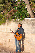 man leaning against a wall playing a guitar
