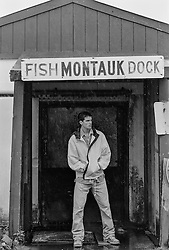 good looking fisherman standing on a dock in the rain