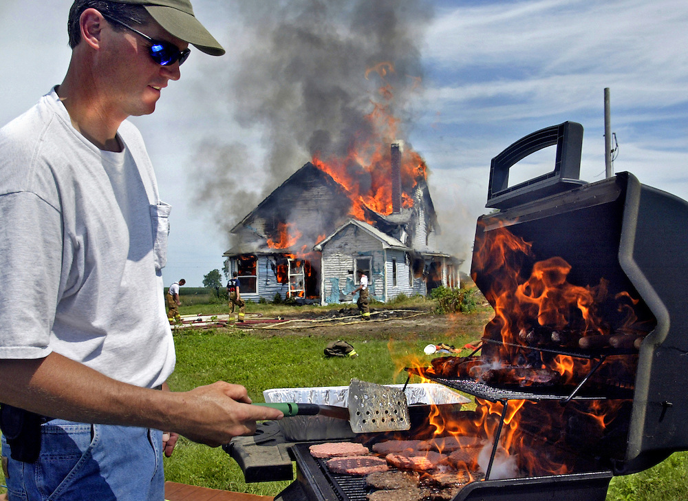 Danville Firefighter Frain (cq) Wagner grills lunch as fellow firefighters burn a house for training Saturday, June 12, 2004, outside Danville, Iowa. Scott Morgan | The Hawk Eye