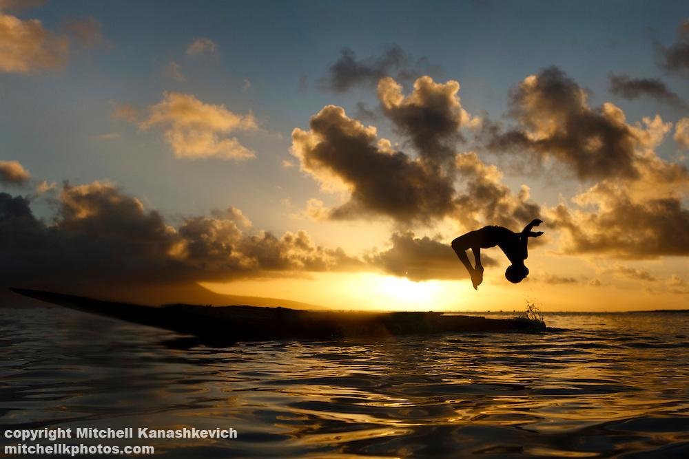 Child doing a backflip from a canoe at sunset. Rah Lava Island, Torba Province, Vanuatu