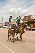 Lady rides horse (Equus caballus) mare with her mule (Mulas mula) colt in Montana Mule Days parade in Montana
