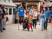 31 JULY 2015 - KATHMANDU, NEPAL: A man and his son join other Buddhists in processing around Bodhnath Stupa. Bodhnath Stupa in the Bouda section of Kathmandu is one of the most revered and oldest Buddhist stupas in Nepal. The area has emerged as the center of the Tibetan refugee community in Kathmandu. On full moon nights thousands of Nepali and Tibetan Buddhists come to the stupa and participate in processions around the stupa. The stupa was heavily damaged in the earthquake of 25 April 2015 and people are no longer allowed to climb on the stupa, now they walk around the base and pray with butter lamps.   PHOTO BY JACK KURTZ