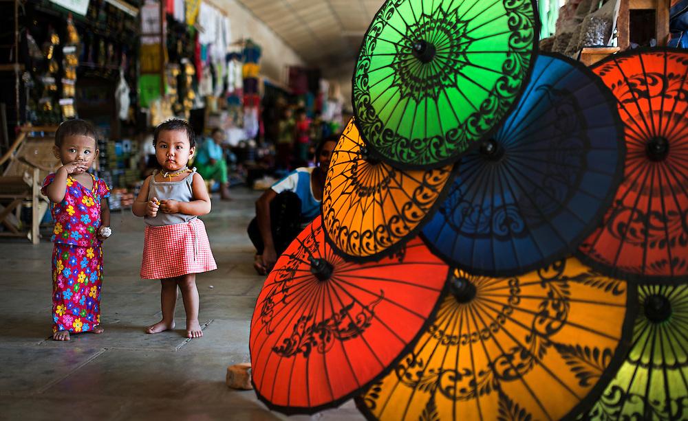 Children near their parents stall selling umbrellas, Myanmar.