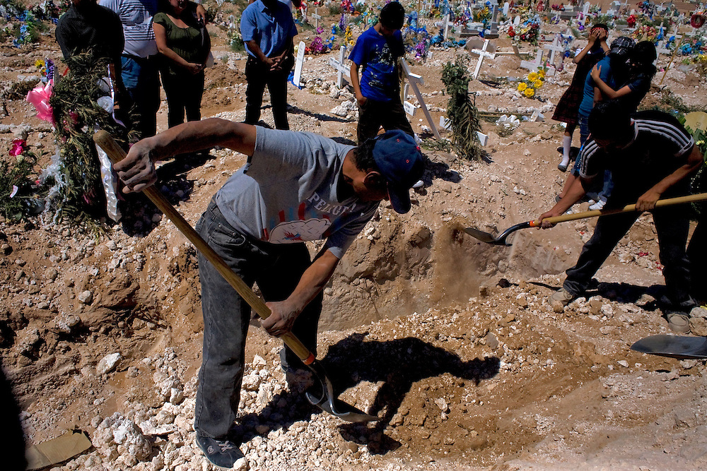 Grave workers bury a Municipal Police officer as family looks on in Ciudad Juarez, Chihuahua on May 21, 2010. The victim was 41-year-old municipal police officer, he was shot outside his home.