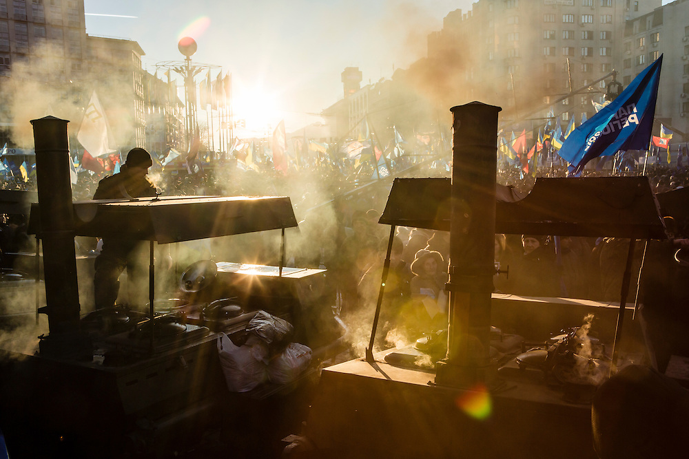 KIEV, UKRAINE - DECEMBER 14: Smoke and steam rise from wood fires heating water to make tea for the crowd at a pro-government rally held by Ukrainian President Viktor Yanukovych's ruling Party of Regionson December 14, 2013 in Kiev, Ukraine. Thousands of people have been protesting against the government since a decision by President Yanukovych to suspend a trade and partnership agreement with the European Union in favor of incentives from Russia. (Photo by Brendan Hoffman/Getty Images) *** Local Caption ***