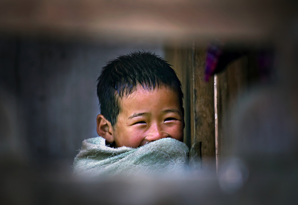 A boy looks out of his home in rural Bhutan.
