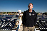 "Greensburg, Kansas, USA..City administrator Steve Hewitt with solar panels on the roof of the Business Incubator. The grain silo stands in the distance...The City of Greensburg and the USDA's Rural Development team joined forces with MVP Architects, BNIM, and engineering firm PEC to create a new business incubator building to provide affordable office space for small, start-up businesses in the town. Five street-level retail shops and nine second-level professional service offices make up the building; a storm shelter is also included. LEED Level: Platinum...""Greensburg: Better, Stronger, Greener!"".On May 4, 2007, an EF5 tornado cut a 1.7-mile path of destruction through Greensburg, Kansas. Winds reaching speeds of 205 miles per hour uprooted trees, demolished homes and leveled the town. Eleven people died and 95% of the buildings were destroyed beyond repair. Residents have since worked furiously to rebuild it in a way that is both economically and environmentally sustainable and to meet the highest environmental standards. Greensburg, whose population has dropped from about 1400 to 800 following the storm and is now growing again, is currently the greenest town in America and the first in the United States to pass a resolution to certify that all city-owned buildings earn LEED Platinum accreditation, the highest level of the LEED rating system...Foto © Stefan Falke"