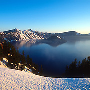 The fog lifts off Crater Lake, Oregon, after a late Spring sunrise, revealing Wizard Island and the deep blue color of the water.