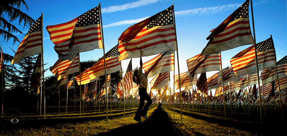 A young girl leaps to touch a flag amongst thousands of others waving in the breeze at the Memorial Field in Gresham, Oregon. The event commemorated those lives lost in the 911 attacks and war in Iraq.