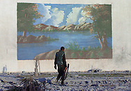 A Palestinian policeman walks by a mural amongst the debris inside a naval installation in Gaza City, in the Gaza Strip, Sunday, May 20, 2001. The naval compound was destroyed by Israeli war planes Friday night. Israel said it used the F-16 war planes _ the first time since the 1967 Mideast war _ to send a message to the Palestinian Authority to rein in militants behind suicide bombings, but Israeli politicians and commentators questioned whether the attacks would have any effect. The Palestinians have said that destroying the Authority's security forces and infrastructure would only exacerbate the situation.