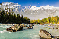 Autumn's colors contrast with winter's first snow in the Chugach Mountains overlooking Eagle River Valley at the Rapids in Chugach State Park in Southcentral Alaska. Morning.