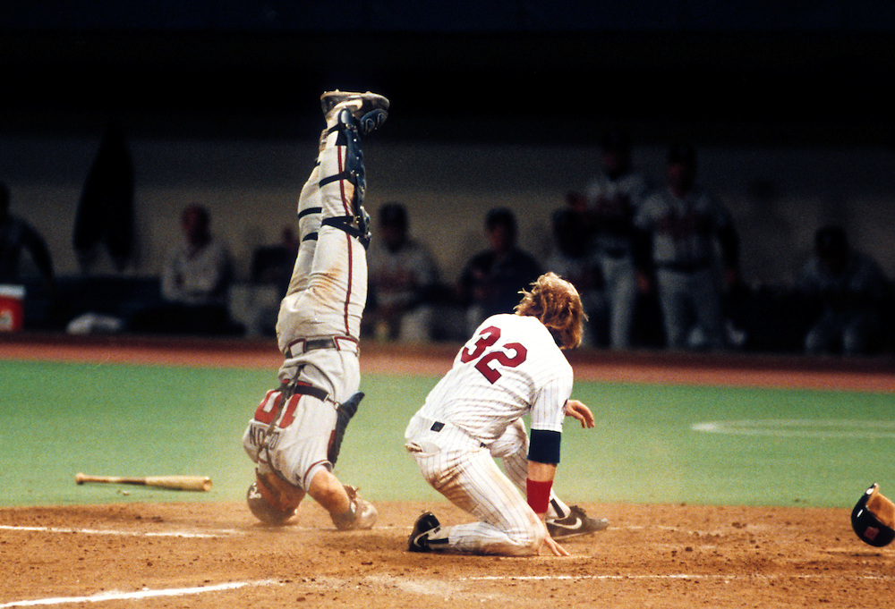 MINNEAPOLIS, MN-OCTOBER 19:  Dan Gladden of the Minnesota Twins bowls over catcher Greg Olson of the Atlanta Braves during Game 1 of the 1991 World Series at The Metrodome on October 19, 1991 in Minneapolis, Minnesota. Gladden was out on the play.  The Twins won the Series 4-3. (Photo by Ron Vesely)