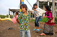 Children play next to one of the few remaining tsunami ruins around the neighborhood of Ulee Lheue on November 20, 2014 in Banda Aceh, Indonesia. The neighborhood sits next to the Indian Ocean shoreline and was hit hard by the 2004 tsunami. Ann Hermes/© The Christian Science Monitor 2014