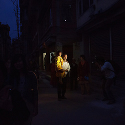 Ramesh Vajracharya carries his daughter, Unika, after her selection as kumari. She is wearing her favorite yellow fleece hoodie with Snoopy on the back, one of the last times she was allowed to wear it. A living goddess can wear only red—the color of creative energy, usually reserved for married women.
