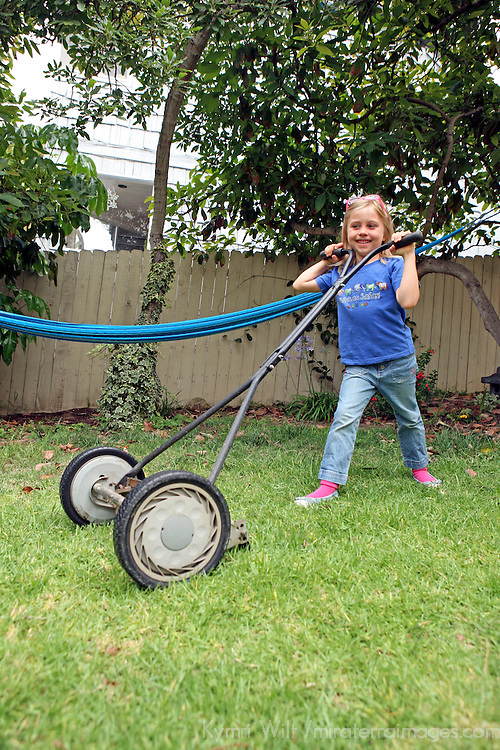 A young girl attempts to mow her own lawn with an environmentally-friendly push reel mower.