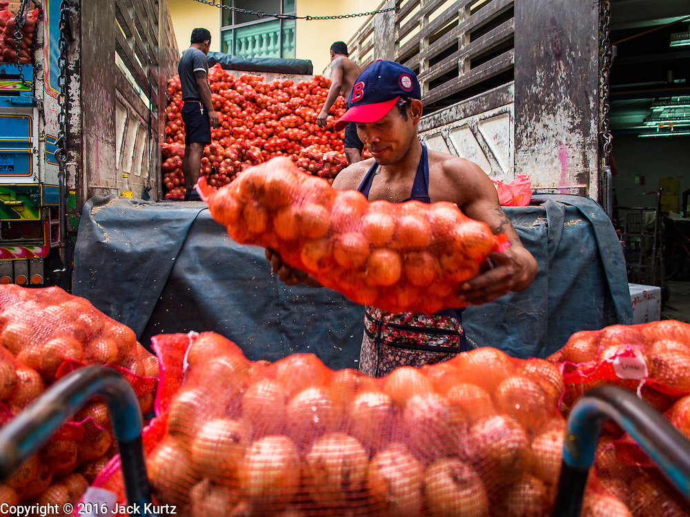 29 FEBRUARY 2016 - BANGKOK, THAILAND:  Workers unload onions in the produce section of the Bangkok flower market. Many of the sidewalk vendors around Pak Khlong Talat, the Bangkok flower market, closed their stalls Monday. As a part of the military government sponsored initiative to clean up Bangkok, city officials announced new rules for the sidewalk vendors that shortened their hours and changed the regulations they worked under. Some vendors said the new rules were confusing and too limiting and most vendors chose to close Monday rather than risk fines and penalties. Many hope to reopen when the situation is clarified.   PHOTO BY JACK KURTZ