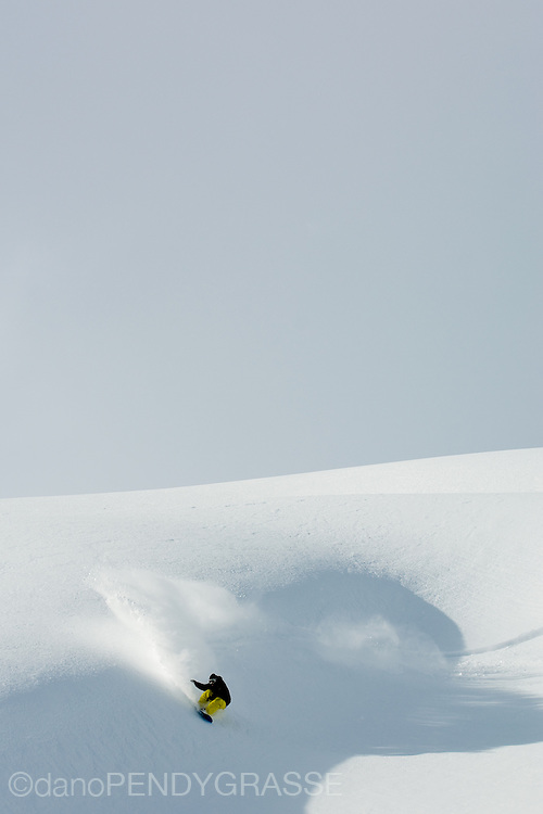 Professional snowboarder Mathieu Crepel lays into a natural wave, sending spray flying, while heli snowboarding in British Columbia.