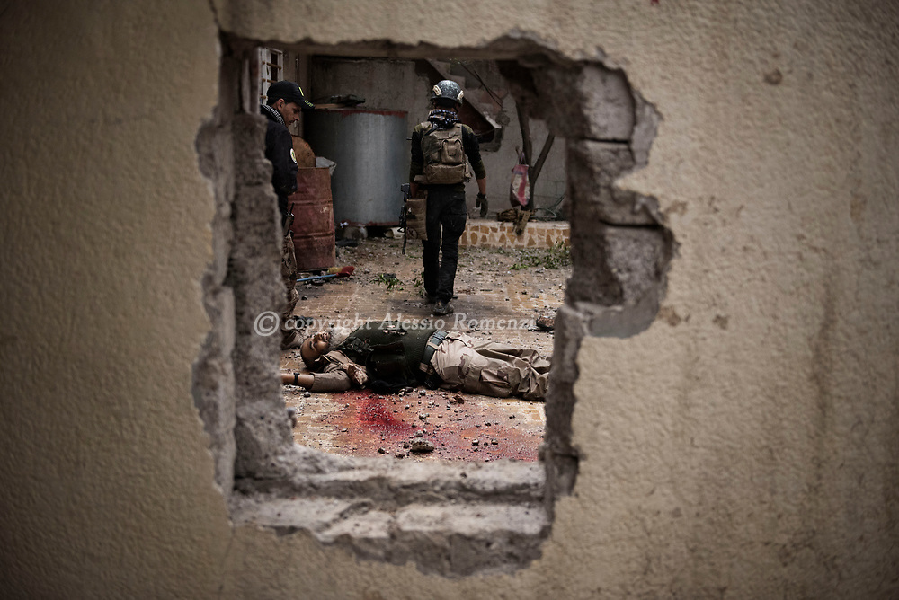 Iraq, Mosul: Golden Division members walk by an ISIS fighter shot dead hours before during an house by house advance in west Mosul. Alessio Romenzi