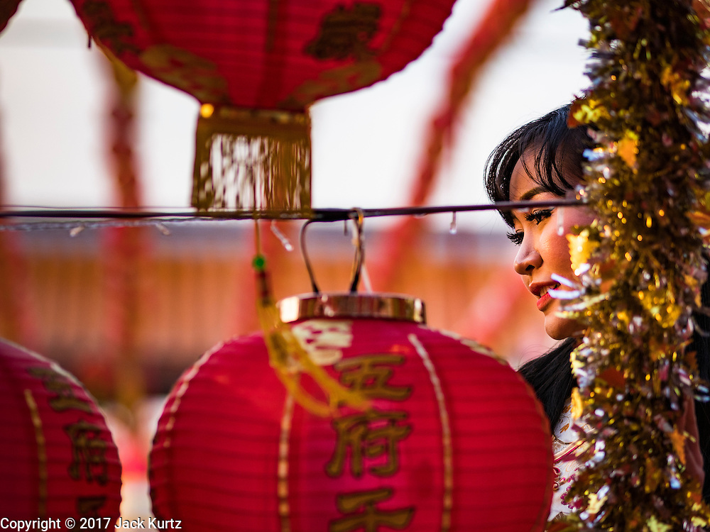 28 JANUARY 2017 - SAMUT PRAKAN, SAMUT PRAKAN, THAILAND: A woman at the Chinese New Year Lantern Festival at the Tham Katanyu Foundation shrine in Samut Prakan, a suburb about 15 miles from Bangkok. More than 5,000 handmade lanterns imported from Taiwan are hung on the grounds of the shrine. Some of the lanterns are traditional Chinese lanterns, others are in the shapes of people or deities. There is also traditional Chinese entertainment, likes lion dances, at the festival.     PHOTO BY JACK KURTZ