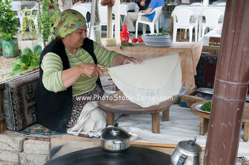 Turkey, Antalya, a Turkish woman preparing a flat bread snack called Gozleme on a Saj an iron dome shaped pan that is used to cook the pita bread on. It is placed over a source of heat, traditionally a wood fire, and the dough is placed on it to cook.
