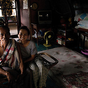 Poonsuk Raman on his house boat in Ayuthaya. He has lived on this boat for twenty years. He is a carpenter, and works in the boatyard by his home. His daughter Siriporn visits him on the weekend. She now lives & works in Bangkok.