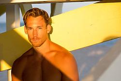 sexy shirtless man under a lifeguard stand at sunset