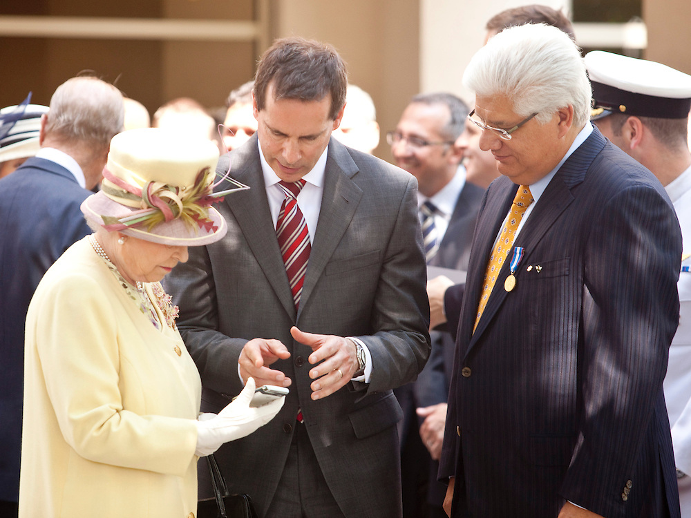 Research in Motion (RIM) CEO Mike Lazaridis and Ontario Premier Dalton McGuinty demonstrate the features of the Blackberry to Queen Elizabeth II as they present her the device following a tour of the RIM facilities in Waterloo, Ontario, July 5, 2010.<br /> AFP/GEOFF ROBINS/STR