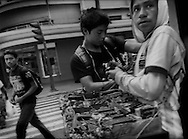 Vulnerable targets for forced gang recruitment: Young men sell sweets, cigarettes, etc. on a street corner in the center of Guatemala City.  Urban crime is one of the primary factors for children migrating to the United States and Guatemala City has one of the highest murder rates of any city in the world. <br /> According to USAID, &quot;2.6 million people &ndash; or 40% of the urban population &ndash; lived in slums. In Guatemala City, slum and non-slum households share neighborhoods on the urban periphery, the dilapidated city center, and in &ldquo;slum islands&rdquo; that are located amidst more affluent, fully serviced areas.&quot;  <br /> Guatemala City is one of the most dangerous cities in the world with a 2013 murder rate of 68.4 homocides per 100,000 people, considerably higher than the American cities of Chicago (18.5/100,000), Los Angeles (7.8/100,000) and New York (5.1/100,000).<br /> <br /> In the 1980's Central American refugees and their children, fled the civil wars which raged in the region, and established gangs, or &quot;maras&quot; in Spanish, in Los Angeles, California before running afoul with law enforcement authorities there.  The gang members were deported back to Central America because of their criminal activity.  Soon maras were soon dominated city streets in Central America's cities.