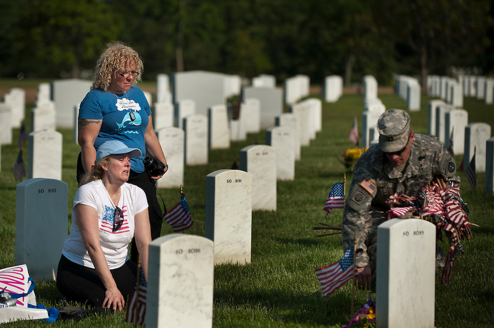 """DIANE FOX (kneeling) and EMILY TORO, both of New York City, look on as a member of the 3rd U.S. Infantry, known as The Old Guard, places an American flag in front of their friend's headstone in advance of the Memorial Day weekend. The tradition, known as """"flags in,"""" is conducted annually since 1948. Every available soldier in the 3rd U.S. Infantry participates, placing small American flags one foot in front and centered before more than 260,000 gravestones and about 7,300 niches at the cemetery's columbarium. Old Guard soldiers remain in the cemetery throughout the weekend, ensuring that a flag remains at each gravestone."""