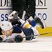 SHOT 3/28/15 7:32:37 PM - The Colorado Avalanche's Nick Holden #2 and the Buffalo Sabres' Marcus Foligno #82 hit the ice after colliding along the boards during their regular season NHL game at the Pepsi Center in Denver, Co. The Avalanche won the game 5-3. (Photo by Marc Piscotty / © 2015)