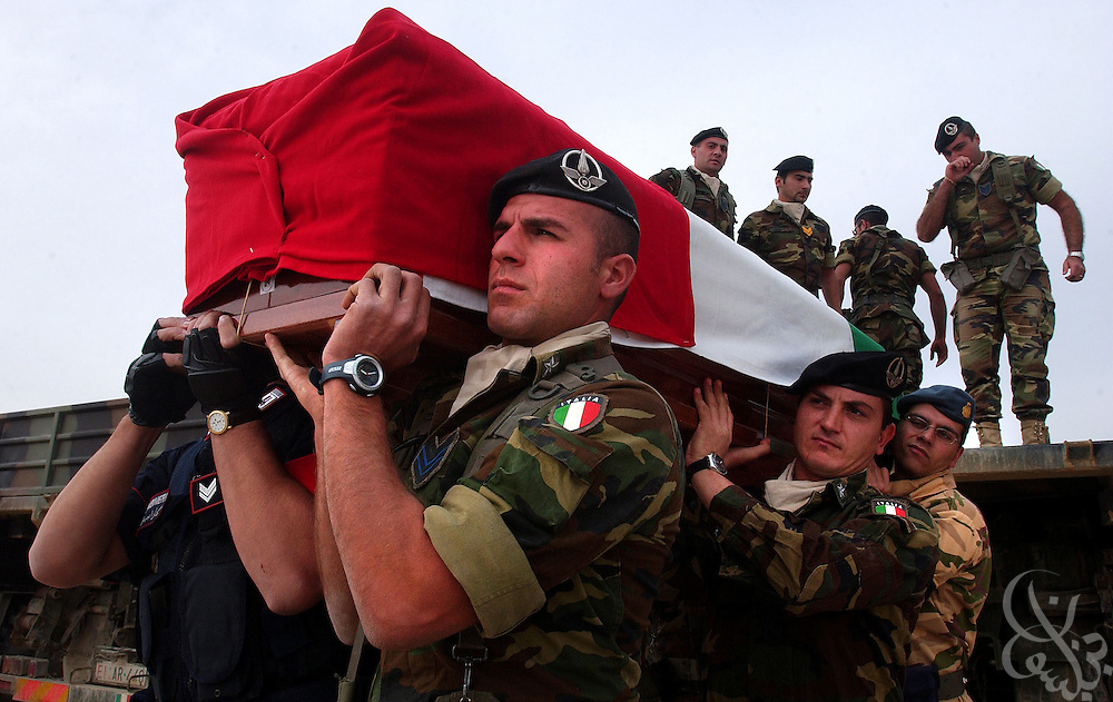Italian carabinieri and soldiers carry a flag draped coffin of their slain comrade during a November 15, 2003 repatriation ceremony at the Tallil airbase in Southern Iraq for 18 Italian nationals killed in the Nasiriyah car bomb attack last week. 16 Italian soldiers and carabinieri members, along with 2 Italian civilians died in the bombing of the carabinieri headquarters in Nasiriyah November 12, 2003. .
